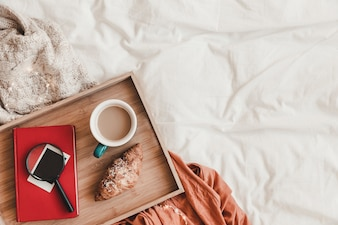 Magnifying glass and book near breakfast food on bed