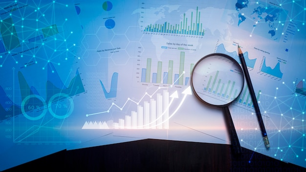 虫眼鏡とドキュメント、テーブル上にある分析データ、およびデジタル仮想現実グラフ