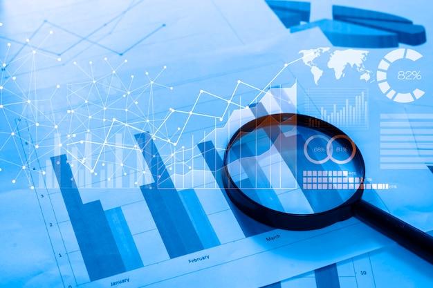Увеличительное стекло и документы с данными аналитики, лежащими на столе