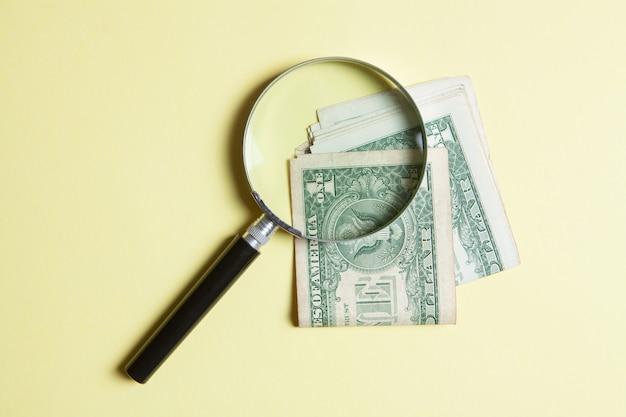 돋보기와 노란색 배경에 돈입니다. 돈 검색 개념