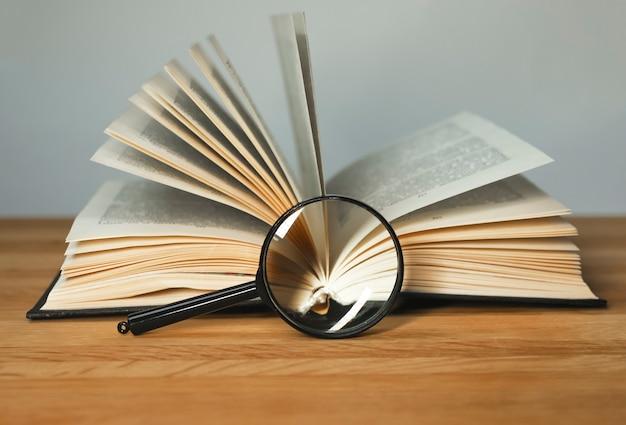 Увеличительное стекло и открытые книги с переворачиванием страниц на деревянном столе, концепция чтения и изучения