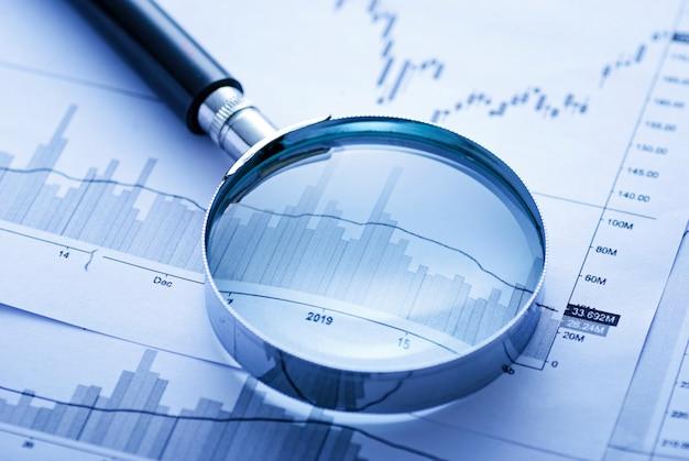 Увеличительное стекло и ручка на бизнес-диаграммах