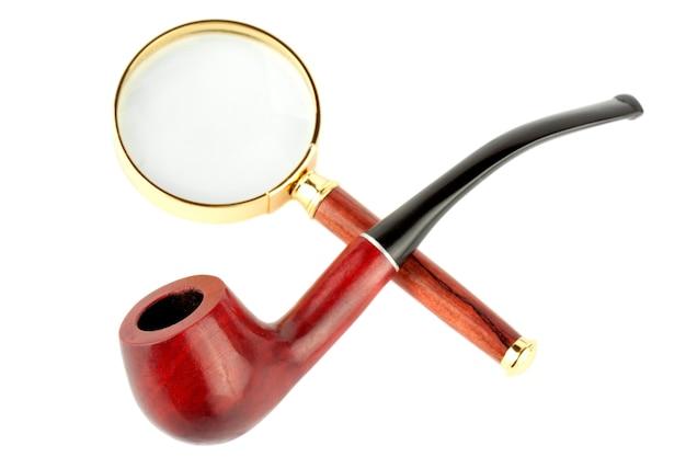 Увеличительное стекло и трубка для табака на белом фоне