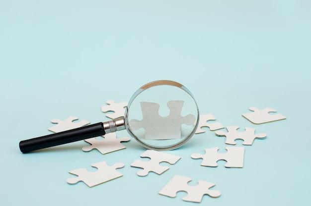Увеличительное стекло и белая головоломка на синем фоне
