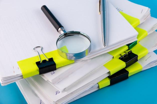 虫眼鏡、メモ用の白い紙のボールペンのクローズアップ虫眼鏡、ドキュメントのスタック上のボールペンのクローズアップ