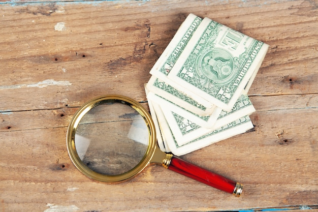 A magnifying glass and a banknote on the table