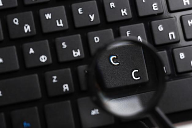 Magnifying glass on black keyboard