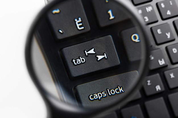 Magnifying glass on black keyboard