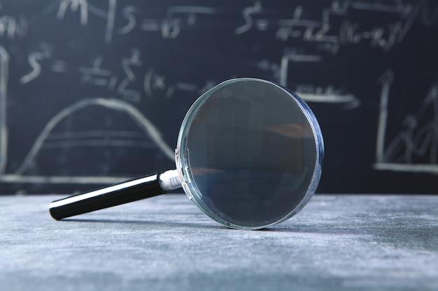Magnifying glass on blackboard background