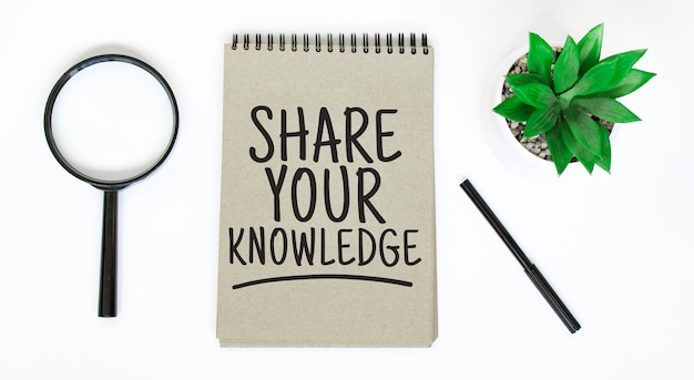 A magnifying glass, a blank brown notebook on a white table. share your knowledge sign
