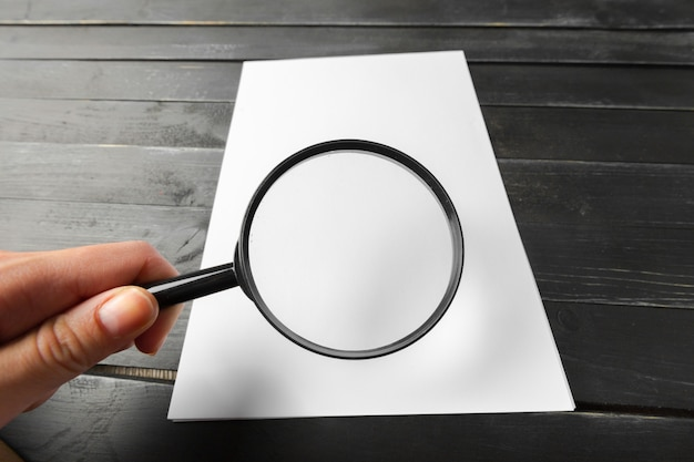 Magnifying glass and blank paper on wooden table