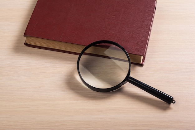 Magnifying glass and book o the wooden