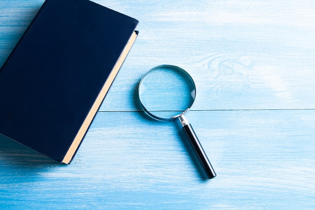 Magnifying glass and book on the table