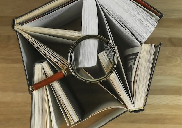 Magnifying glass over books on wood table top view reading and studying concept