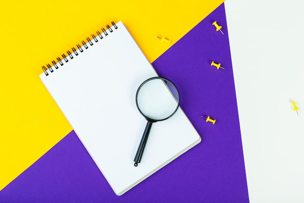 Magnifying glass on bright colored  flat lay