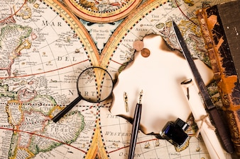 Magnifying glass, burnt paper, pen and ink bottle, knife and coins on world map