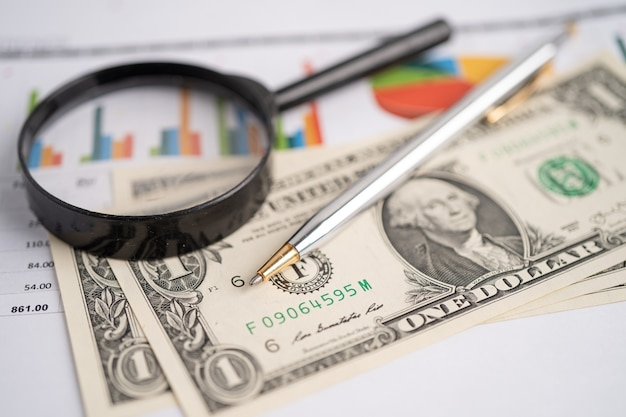 Magnifying glass on charts graphs paper financial development