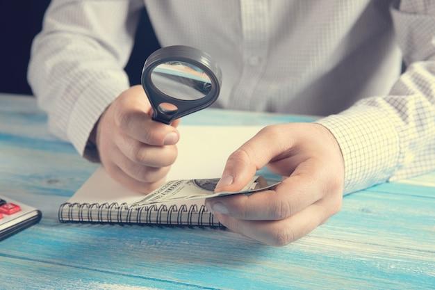 Magnifying glass checks money .