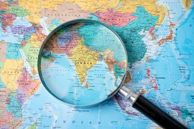 Magnifying glass close up with colorful world map