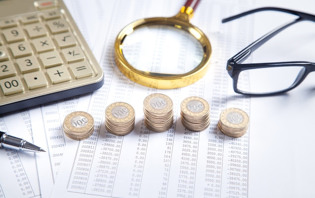 Magnifying glass, coins, eyeglasses, calculator, pen on financial documents. business. finance
