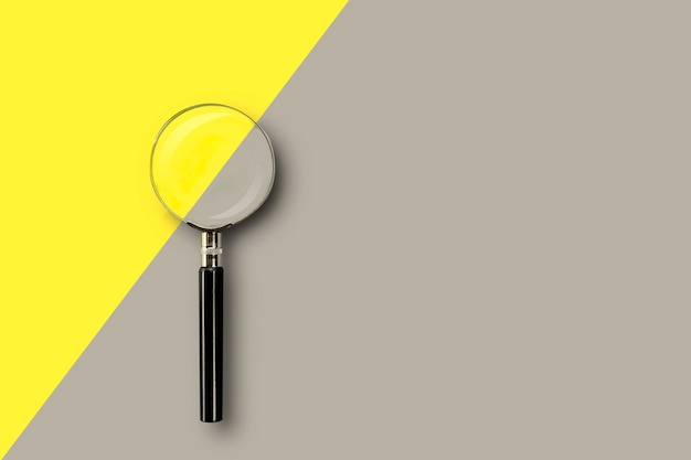 Magnifying glass on colored yellow-gray background with place for text