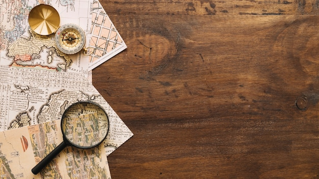 Magnifying glass and compass on maps