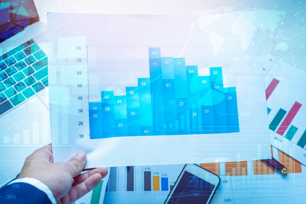 Magnifying glass and documents with analytics data lying on table, business finance background