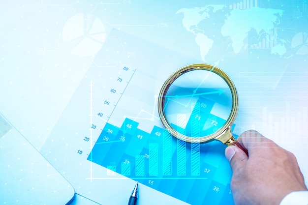 Magnifying glass and documents with analytics data lying on table, business finance