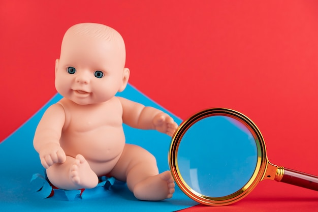 Magnifying glass and a doll on a red and blue background. copy space.