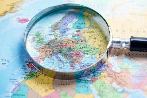 Magnifying glass on europe world globe map background.