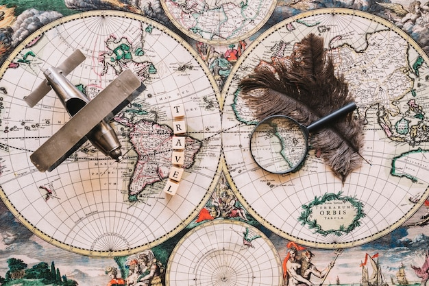 Magnifying glass and feathers near travel writing and plane