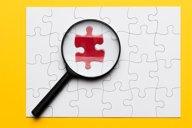 Magnifying glass focusing on red puzzle piece connected with white piece