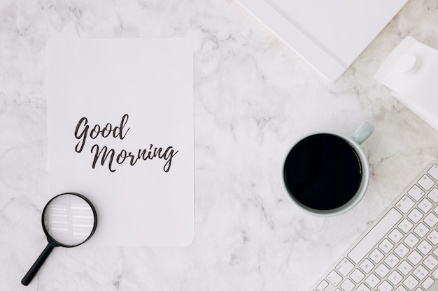 Magnifying glass on good morning paper with coffee cup; diary and keyboard on white marble desk