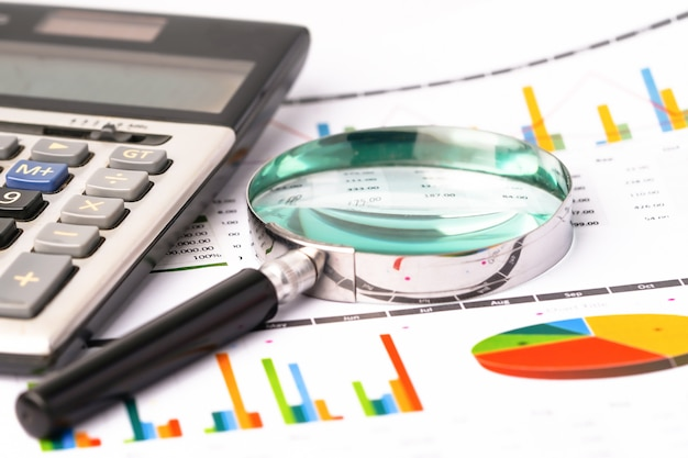 Magnifying glass on graphs spreadsheet paper with calculator.