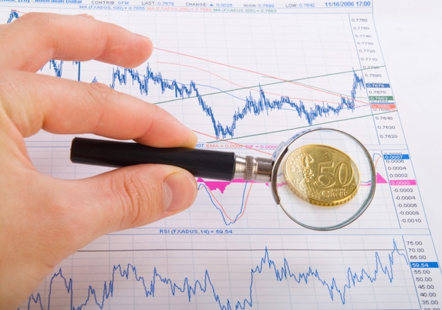 Magnifying glass in hand and euro coin on business charts