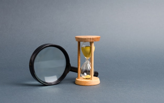 Magnifying glass and hourglass. search for time