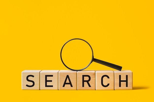 Magnifying glass and the inscription search on a yellow background