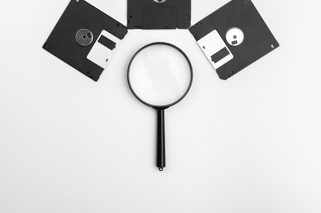 Magnifying glass inspecting on floppy disk concept