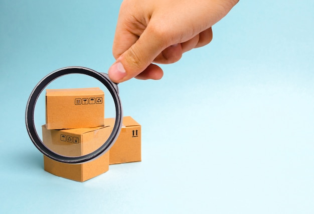 Magnifying glass is looking at the bunch of boxes on a blue background.