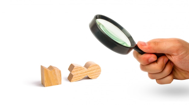 Magnifying glass is looking at a wooden figure of a man is broken.