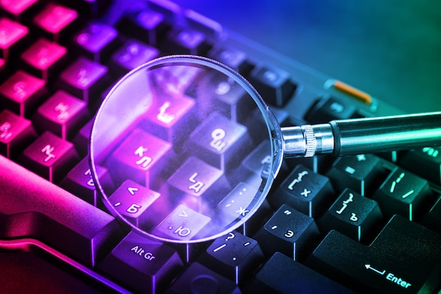 Magnifying glass on the keys of a black computer keyboard in neon light