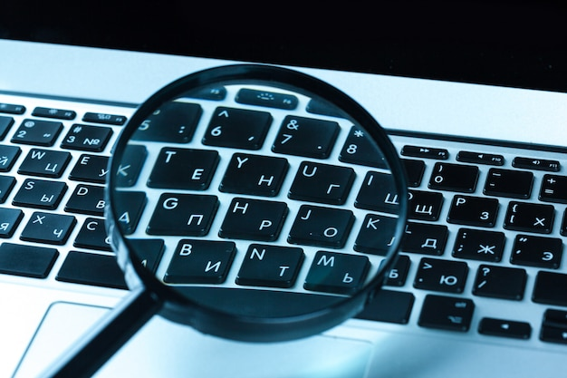 Magnifying glass on laptop computer.