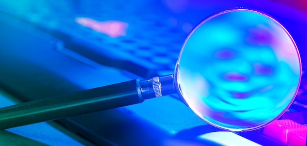 Magnifying glass on laptop keyboard in neon light.