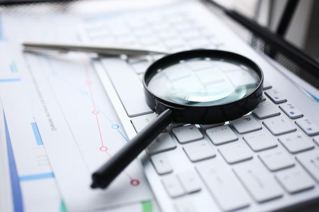 Magnifying glass lies on white keyboard Premium Photo