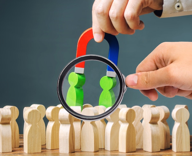 A magnifying glass looks at a magnet pulls green figures of people out of the crowd