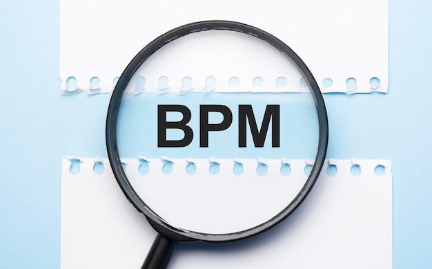 青いテーブルの2枚の紙の間に記号bpmが付いた虫眼鏡ルーペ。