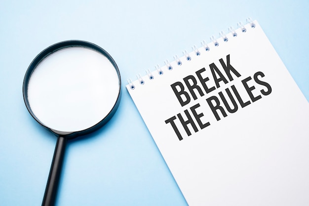 Magnifying glass loupe with sign break the rules blue table.