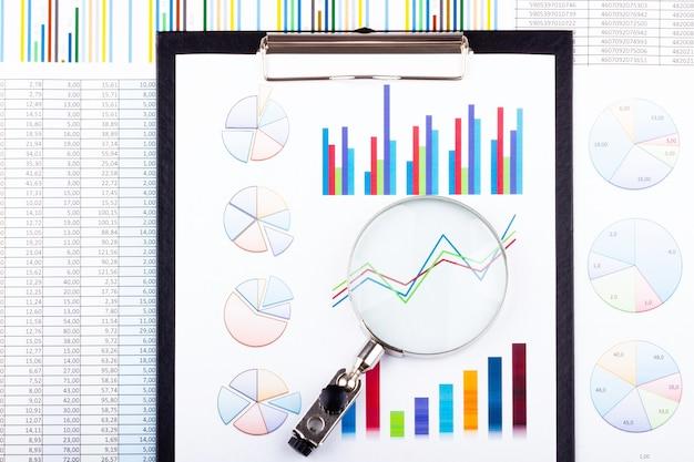 Увеличительное стекло, лежащее на бизнес-диаграммах
