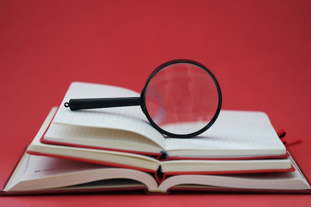 Magnifying glass lying on pile of books on red background closeup