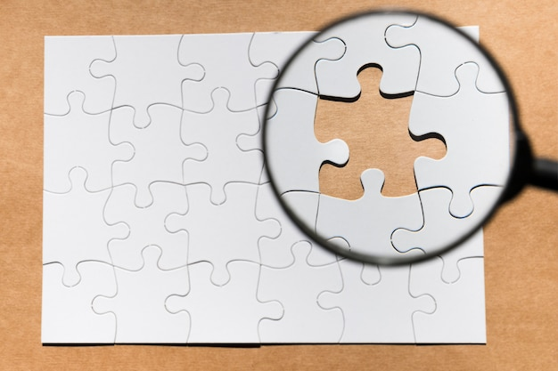 Magnifying glass on missing puzzle over brown paper textured backdrop